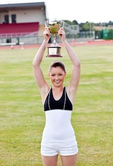 Netter weiblicher athlet, der ein trophee hält