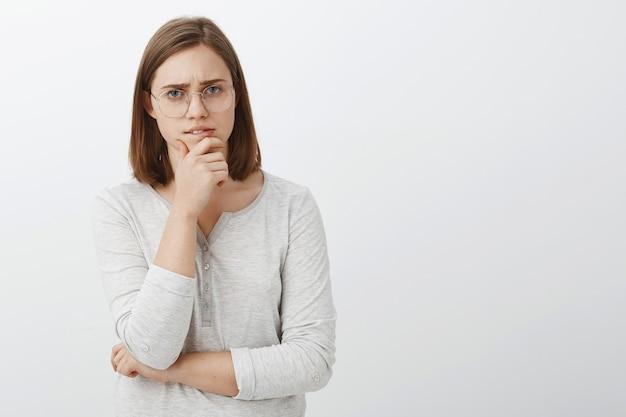 Netter weiblicher geek, der versucht, hartes mathe-rätsel zu lösen, das nachdenklich über weißer wand steht, die kinn reibt, während brainstorming schaut, während entscheidung trifft oder über graue wand posiert