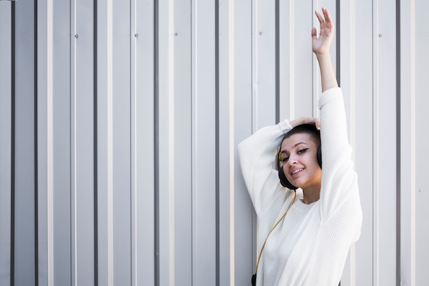 Netter weiblicher jugendlicher in den kopfhörern mit dem arm angehoben