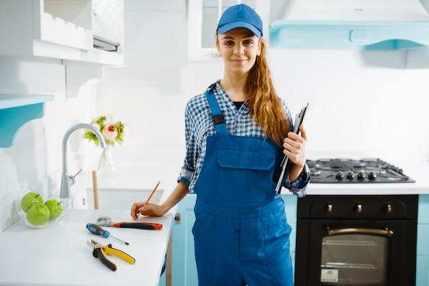 Netter weiblicher möbelhersteller in der uniform hält notizbuch in der küche.