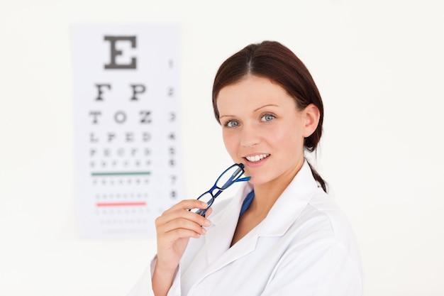 Netter weiblicher optiker mit einem sehtest