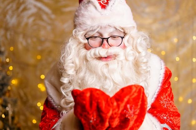 Netter weihnachtsmann in gläsern auf einem wandhintergrund mit einem hellen girlandenbokeh hände in handschuhen nah...