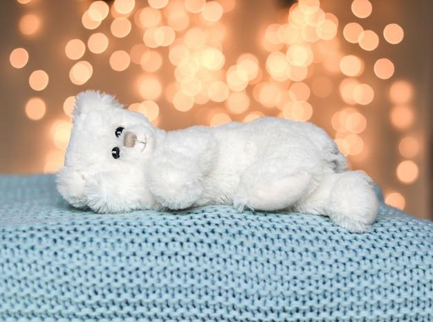 Netter weißer kleiner teddybär, der friedlich auf hellblauer gestrickter decke liegt. gemütlicher pullover