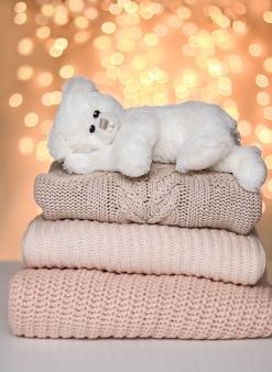 Netter weißer kleiner teddybär, der friedlich auf stapel der gestrickten strickjacken liegt.