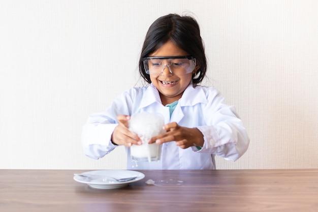 Netter wissenschaftler des kleinen mädchens, der ein experiment leitet