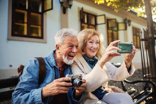 Nettes älteres paar, das auf der bank sitzt und ein selfie macht. mann hält kamera, während frau ein handy hält.