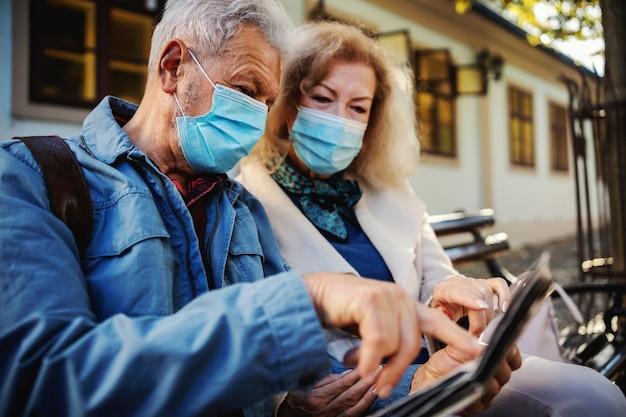 Nettes älteres paar mit schutzmasken beim sitzen auf der bank und beim betrachten der karte. der mensch zeigt auf etwas, das er in der innenstadt besuchen möchte.