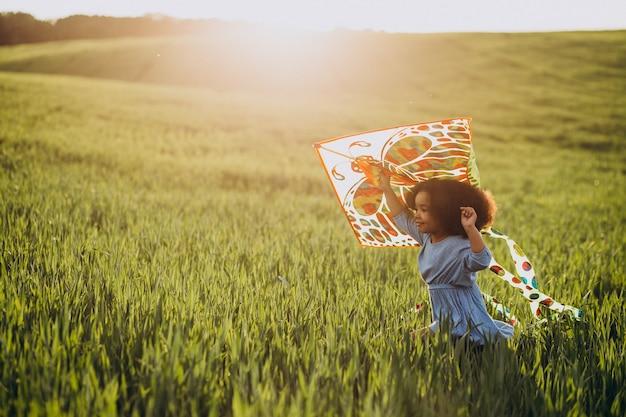 Nettes afrikanisches babymädchen auf dem feld auf dem sonnenuntergang, der mit drachen spielt
