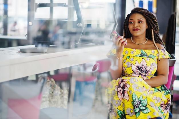 Nettes afroamerikanermädchen der kleinen höhe mit dreadlocks, abnutzung an farbigem gelbem kleid, sitzen auf café im einkaufszentrum und sprechen am telefon.