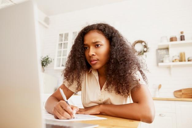 Nettes afroamerikanisches studentenmädchen mit ernstem blick, der hausaufgaben am esstisch macht, vor offenem laptop sitzt und notizen mit stift macht. stilvolle schwarze frau, die elektronisches gerät für fernarbeit verwendet