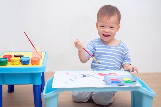 Nettes asiatisches 1-jähriges kleinkindjungenkind, das mit pinsel u. aquarellen zu hause malt, kreative kunstaktivitäten für körperliche entwicklung, großes und kleines muskelentwicklungskonzept der kinder