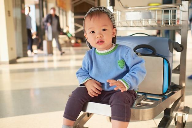 Nettes asiatisches 2 jahre altes kleinkindjungenkind mit koffer, sitzend auf trolley am flughafen, familienreise u. urlaub mit kinderkonzept