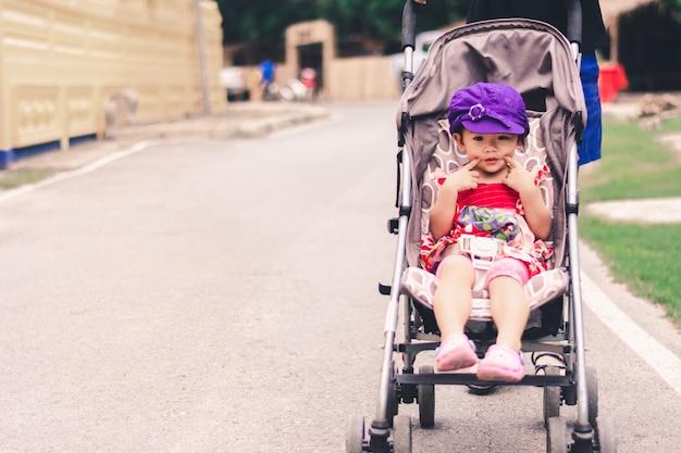 Nettes asiatisches baby, das auf kinderwagenwagen sitzt und das lächeln aufwirft