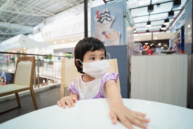 Nettes asiatisches baby, das chirurgische maske trägt und auf dem stuhl sitzt, der eis im restaurant wartet