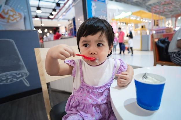 Nettes asiatisches baby, das eis im restaurant isst