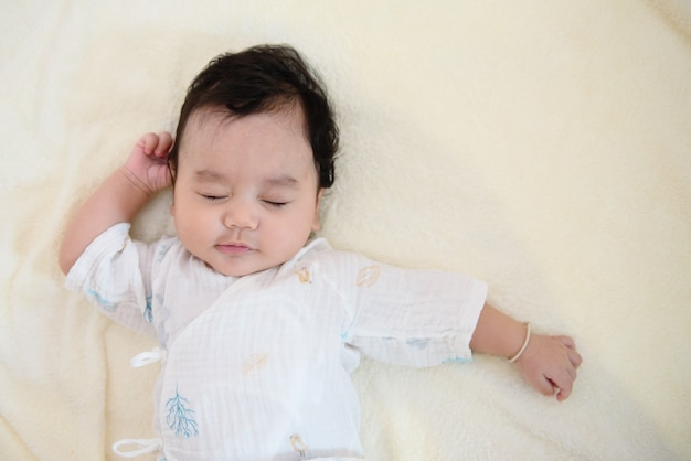 Nettes asiatisches baby, das ihre augen schließt, die auf dem bett liegen