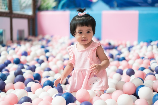 Nettes asiatisches baby, das mit vielen bällen spielt