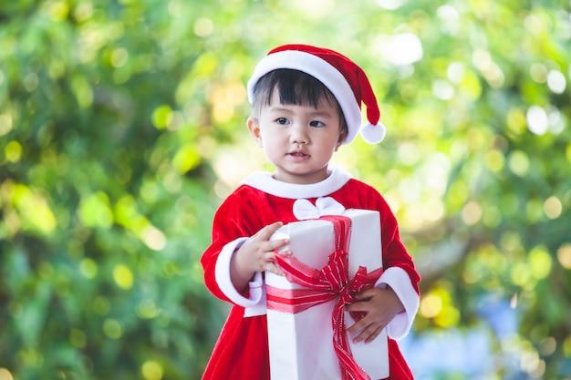 Nettes asiatisches baby, das sankt-anzug in der hand hält schöne geschenkbox trägt