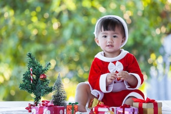 Nettes asiatisches Baby, das Sankt-Anzug mit schönen Geschenkboxen auf Weihnachtsfeier trägt