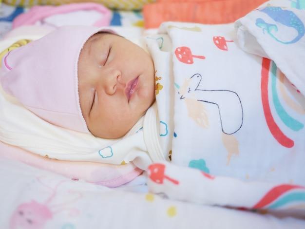 Nettes asiatisches baby schlafend eingewickelt in eine decke auf dem bett