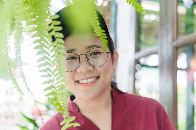 Nettes asiatisches fettes jugendlich lächeln mit glücklichem ausdruck der gläser mit dem guten gesunden weißen zahn