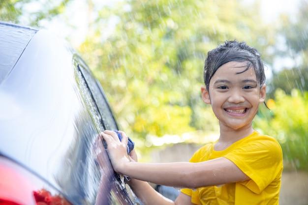 Nettes asiatisches kind, das am sommertag ein auto mit schlauch wäscht