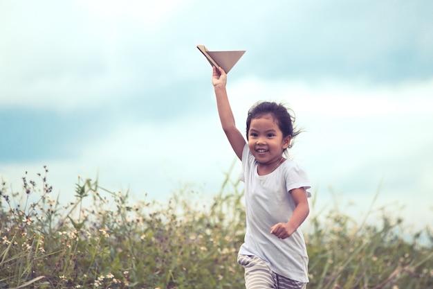 Nettes asiatisches kind, das spielzeugpapierflugzeug in der wiese im weinlesefarbton spielt