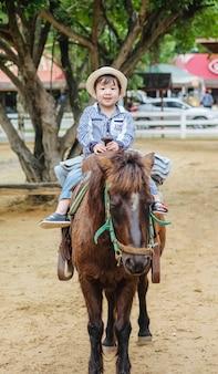 Nettes asiatisches kind der nahaufnahme, das ein pferd im bauernhofansichthintergrund reitet