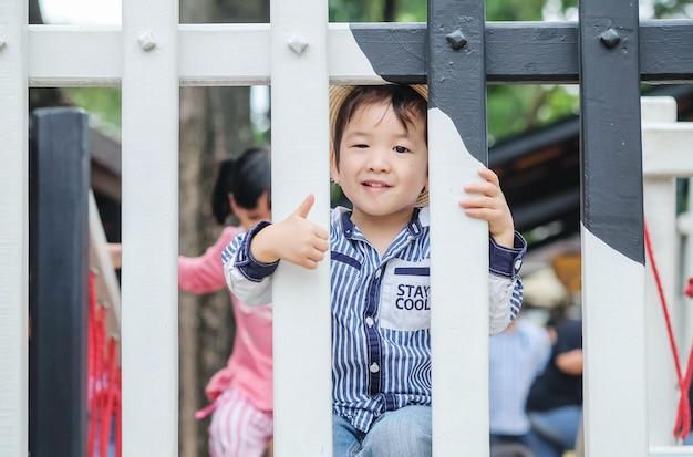 Nettes asiatisches kind der nahaufnahme mit lächelngesicht und -daumen oben in den großen durchschnitten auf einer hölzernen brücke im spielplatzhintergrund