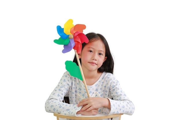 Nettes asiatisches kind des kleinen mädchens mit dem bunten windrad lokalisiert auf weißem hintergrund. kind hält windmühle und sitzt auf stuhl. bild mit beschneidungspfad