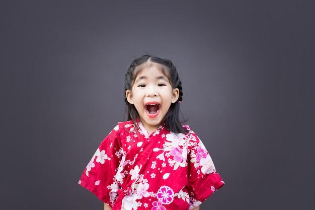 Nettes asiatisches kind mit japanischem stilkleid