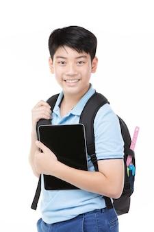 Nettes asiatisches kind mit schulrucksack und -tablette