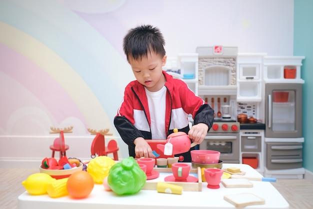 Nettes asiatisches kindergartenjungenkind, das spaß hat, allein mit kochendem spielzeug zu spielen