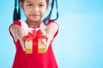 Nettes asiatisches Kindermädchen, das in der Hand schönes Geschenk auf Weihnachtsfeier hält