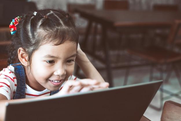 Nettes asiatisches kindermädchen, das auf laptop im café mit spaß und glück verwendet und spielt