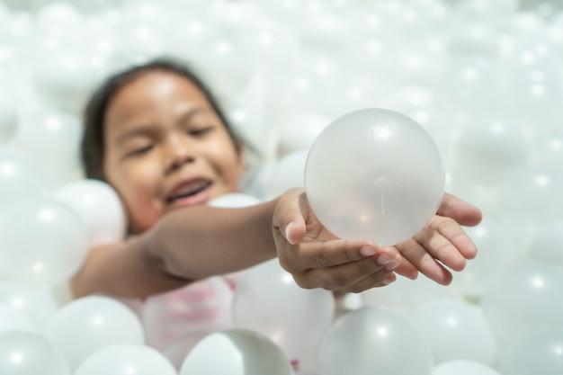 Nettes asiatisches kindermädchen, das den ball hält und spaß hat, mit weißen plastikbällen zu spielen