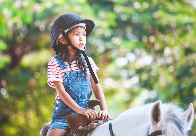 Nettes asiatisches kindermädchen, das ein pferd im bauernhof mit spaß reitet