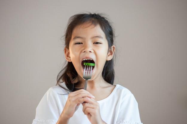 Nettes asiatisches kindermädchen, das gesundes gemüse mit gabel isst