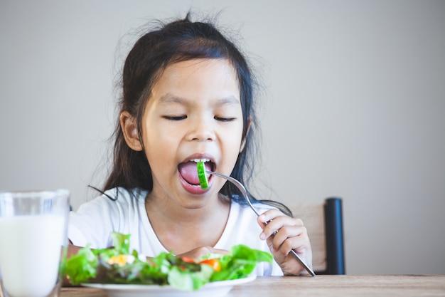 Nettes asiatisches kindermädchen, das gesundes gemüse und milch für ihre mahlzeit isst