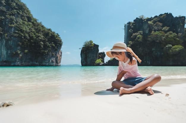 Nettes asiatisches kindermädchen, das hut und sonnenbrille trägt, sitzt am strand und spielt mit sand.
