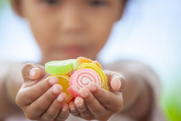 Nettes asiatisches kindermädchen, das in der hand geleesüßigkeiten hält und zu anderem teilt