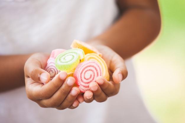Nettes asiatisches kindermädchen, das in der hand geleesüßigkeiten hält