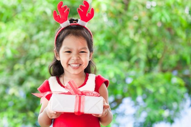 Nettes asiatisches kindermädchen, das in der hand weihnachtsgeschenk hält