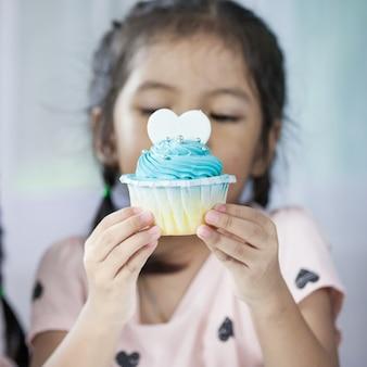 Nettes asiatisches kindermädchen, das köstlichen blauen kleinen kuchen anhält