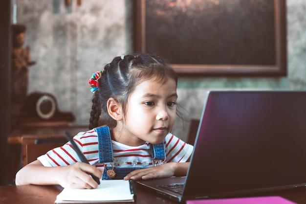 Nettes asiatisches kindermädchen, das laptop verwendet und auf ihr notizbuch in das café schreibt