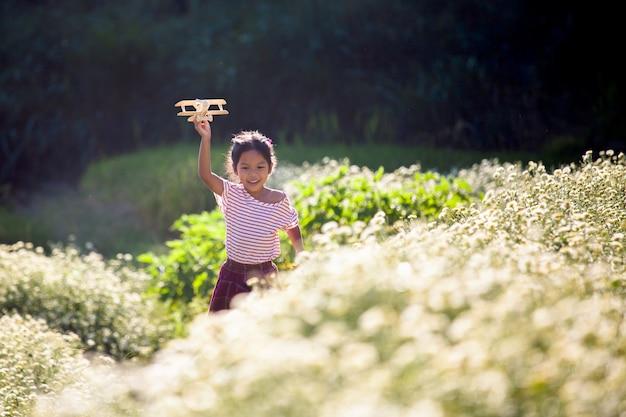 Nettes asiatisches kindermädchen, das mit hölzernem flugzeug des spielzeugs auf dem blumengebiet läuft und spielt
