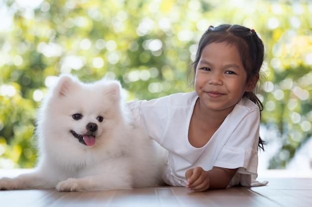 Nettes asiatisches kindermädchen, das mit ihrem spitzhund mit spaß und glück spielt