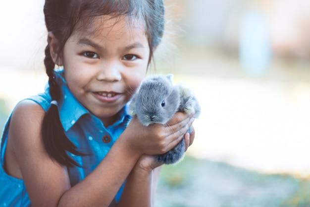 Nettes asiatisches kindermädchen, das mit kleinem häschen mit liebe und weichheit spielt