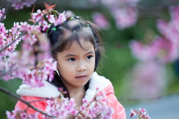 Nettes asiatisches kindermädchen, das mit schönem rosa kirschblütengarten genießt