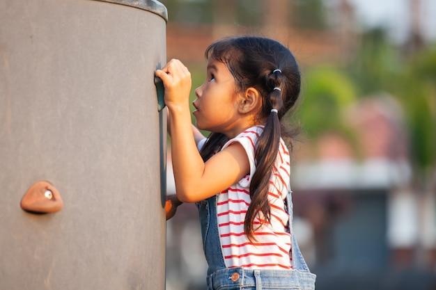 Nettes asiatisches kindermädchen, das spaß hat, auf der felsenwand im spielplatz zu spielen und zu klettern